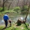 Grandpa and Gabe throwing rocks in the river